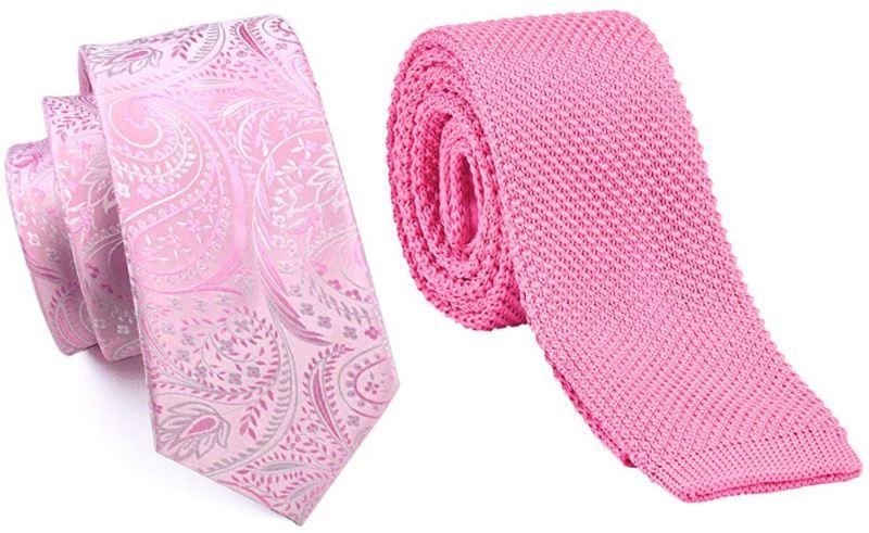 2 corbatas de color rosa enrolladas. La primera es de color rosa pastel de seda, lisa y con motivos florales. La segunda corbata es rosa fucsia y el tejido es de punto.