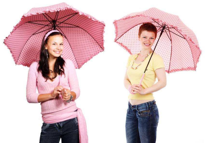 Mujeres jóvenes sonrientes con paraguas rosas con topos en tonos rosados más oscuros
